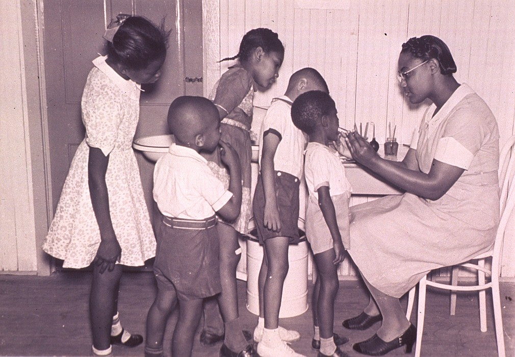 An old photo of a Black medical professional treating a young Black child.